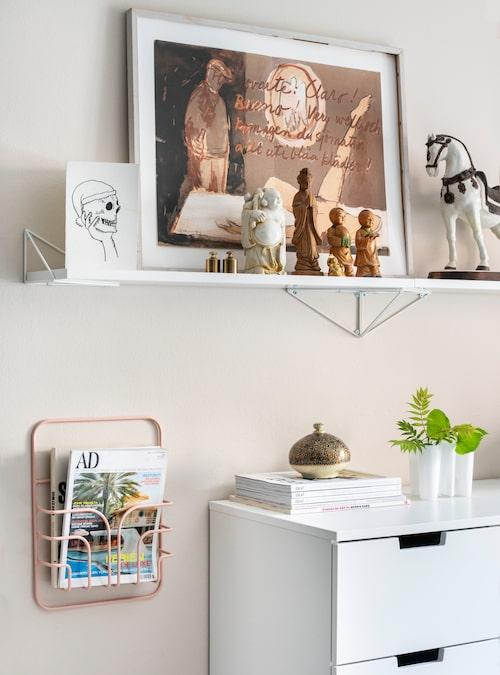 Vackert på väggen. Lotta tycker att det kul med konst och bilder, och använder lägenhetens alla väggar till det. Tavlan är en litografi av Gösta Werner. Hyllor och tidningsställ kommer från Maze. Byrå från Ikea. Hästen är ett reseminne från Italien.