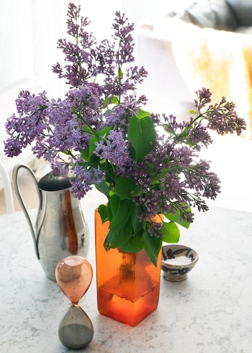 Fynd & reseminnen. På matbordet står en orange vas från loppis tillsammans med en karaff från Georg Jensen, en liten marockansk skål och ett timglas från Hay.