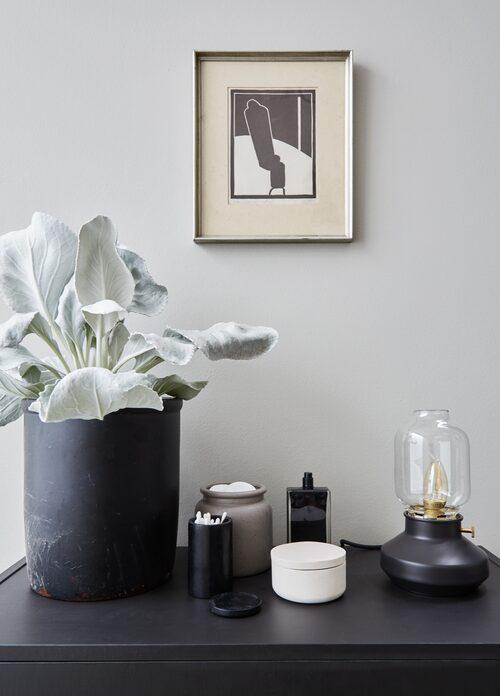 Bordslampa från Ikea och blandade keramikföremål bildar ett enkelt och harmoniskt stilleben i badrummet.
