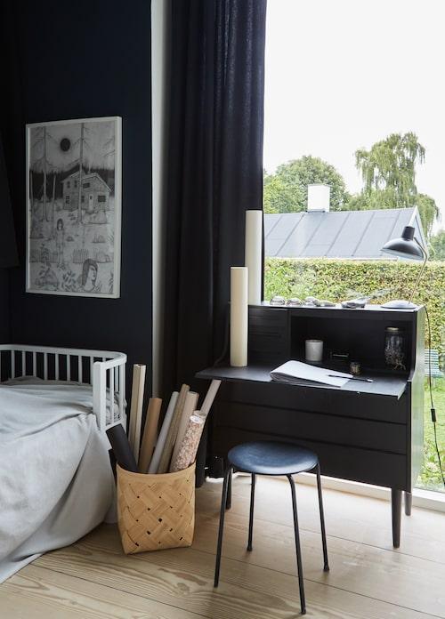 Ingrids rum har svarta väggar och gardiner - med så mycket fönster är det ingen risk att det känns mörkt. Sekretär och pall är ommålade loppmarknadsfynd. Poster av Ragnar Persson från Ikea, limited edition. Korg från Lillerød.