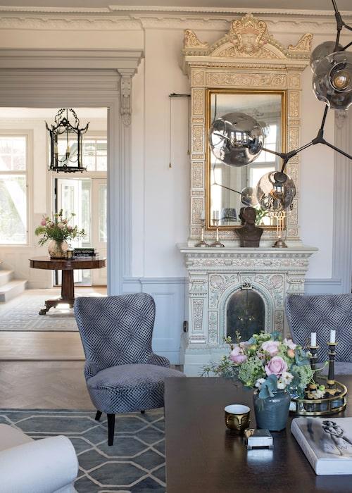 De vackra panelerna och listverken framhävs med ljusgrå kulör. Genom dörröppningen skymtar den pampiga entréhallen.