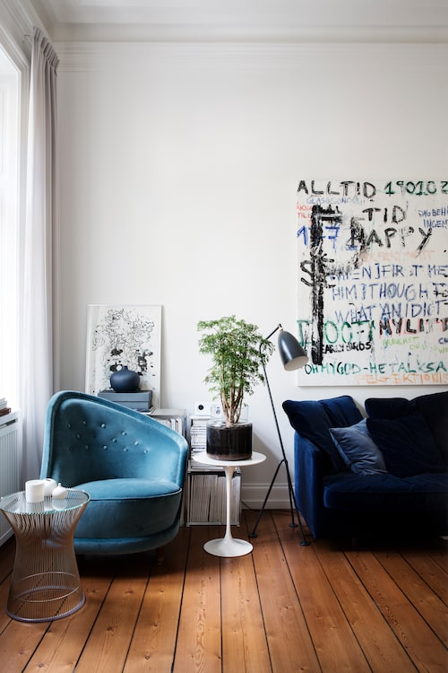 Den asymmetriska fåtöljen är ett fynd från Myrorna, då i fläckad gul sammet, numera omklädd i behagligt blått till loungerummets färgtema. Det lilla vita Tulipbordet följde med hem från London som handbagage. Den stora tavlan har Johanna och Alexander gjort.