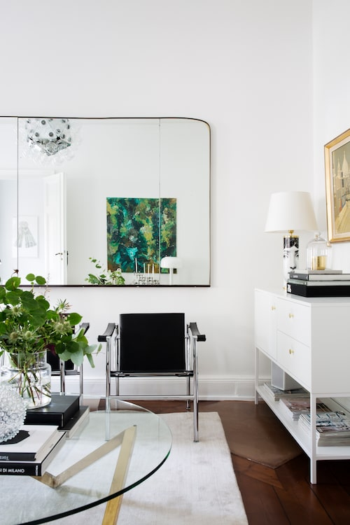Rymden i vardagsrummet förstärks med hjälp av en fransk vintagespegel. Le Corbusier-fåtöljerna är köpta av Alexander i London. Matta från Knut mattor, sideboard Vita från Voice, Fornasettilampa från Svenskt tenn.