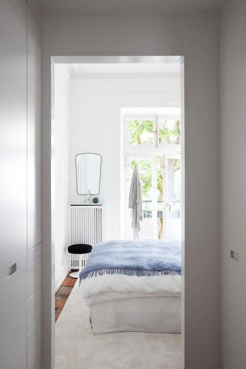 Det ljusa sovrummet har utgång till balkong. Johanna gillar speglar med form, denna från antikaffär. Tulippall från Knoll. Hängaren kommer från Alex föräldrahem, tidigare knallgul och sliten, numera vitmålad. Den gosiga blå filten är från Nordiska galleriet.