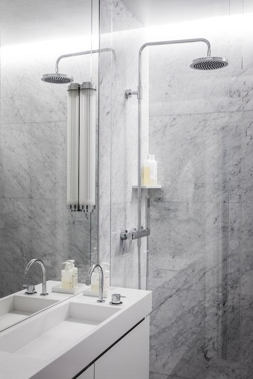"""Badrummet är Alex """"baby"""" som han ritat själv. På väggen tre marmorskivor, likadant på golvet. Dusch, Dornbracht, kran av Arne Jacobsen, Vola. Lampan i art deco-stil är köpt i London."""