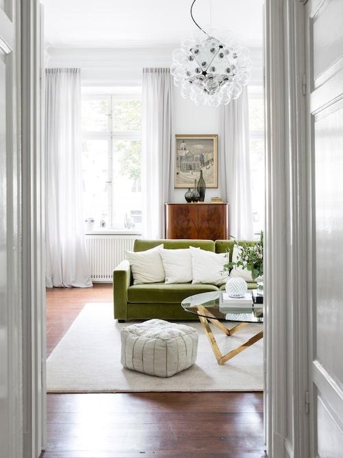 Vardagsrummets gröna sammetssoffa har hängt med länge. Soffbord köpt i en vintagebutik, sittpuffen är från 70-talet. Taklampa Taraxacum från Flos, köpt i London. Gardiner uppsydda i ull- och silkesblandning hänger i alla fönster som vetter mot Karlavägen. Tavlan och barskåpet i teak har Johanna ärvt av sin farfar. Vaser från Ikea.