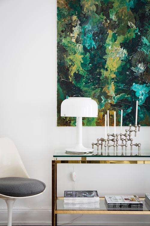 Under den gröna tavlan, som Johanna fått av sin farfar och tyckt om sedan hon var liten, står bordslampa Knubbling, Ateljé lyktan, och Nagelljus-stake från Stoff. Sideboard i glas och mässing från en nedlagd butik.