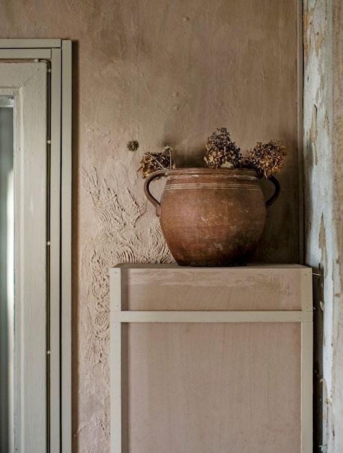 """En piedestal i egen design som Soraya snickrat ihop själv, ovanpå står en gammal antik urna med några torkade kvistar hortensia. Väggen bakom är ett exempel på Sorayas lekfulla attityd till väggarna: """"Jag brukar blanda färgen själv, ofta använder jag flera olika. Ibland jobbar jag med spackel och gipsbruk som jag sen målar på."""""""