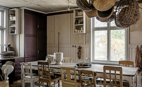 Trots sina olikheter passar stolarna alldeles förträffligt tillsammans: Matbord från Frankrike med plats för många. Runt bordet står ett gäng loppisfyndade stolar. I väggpanelernas överkant har Soraya satt knopplister för förvaring av kökshanddukar, förkläden och köksredskap.