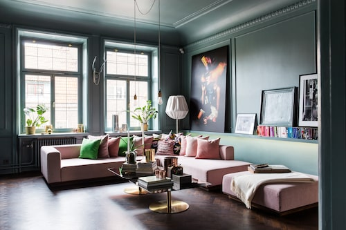 Skönt grönt. Den gröna färgen sätter tonen i vardagsrummet. Väggar, listverk och tak, allt har målats i samma nyans, NCS S 5010-B30G. Belysningen är klurigt fixad, med spottar i fönstret, på skena i taket och under bänken bakom soffan. Golvet är original men var trist brungult, så paret lät slipa det och betsa det mörkbrunt. Soffa, Bolia, soffbord Flash från Tom Dixon, kuddar från bland annat Svenskt tenn, filt, Hermès. Stor tavla från The old biscuit mill market i Kapstaden, Sydafrika, mellanstor tavla av Anders & Yvette Dahlbom från Wettergren galleri. Taklampor, Buster + Punch, golvlampa Baklava, av Claesson Koivisto Rune/Örsjö.