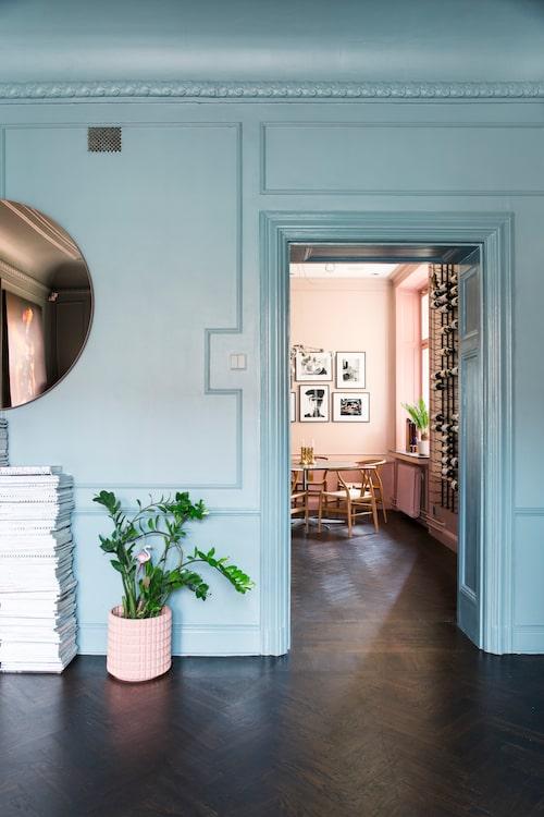Den här väggen tänkte paret riva, men den var bärande, så det gick inte. Väggen har samma gröna nyans som övriga vardagsrummet men ser blå ut här, beroende på hur ljuset faller.