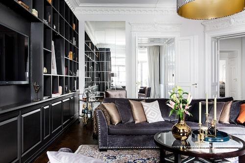 Imponerande takhöjd, originalstuckatur och spegelvägg. Vardagsrummet andas både förra sekelskiftet och 2010tal. Soffor från Mio, taklampa klädd i tyg från GP&J Baker. Barvagn och persisk matta inropade på Bukowskis. Fåtölj från Ruth & Joanna. Soffbord, Englesson. Mattan är en langetterad heltäckningsmatta. I soffan, brun och svart kudde från Smaller objects. På soffbordet, bricka från Ruth & Joanna, ljusstake, Posh living, guldvas från Bohem, tre småljusstakar i guld från Straight design/Bedazzled. Barvagn, Bukowskis.
