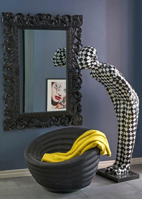 I hallen hälsar en schackrutig skulptur välkommen, Kare design. Puff, Hay, ornamenterad spegel, The one.