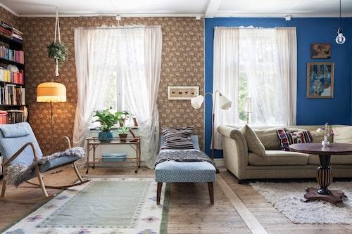 """I vardagsrummet krockar tapet och blå vägg på ett roligt sätt. """"Vi tyckte att det var synd att måla över tapeten och kunde inte få tag på fler rullar så den fick vara kvar. Det är kul att se spår från förr"""", säger Elin."""