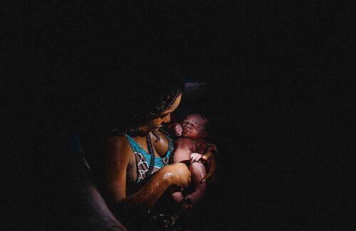 """Fotograf Linnéa Geiger om bilden: """"Förlossning där mamman inspekterar barnet i några minuter innan adoptivmamman kommer och tar över."""""""
