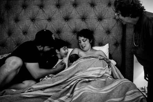 """Fotograf Linnéa Geiger om bilden: """"Att föda hemma har sina fördelar, som att krypa ner i sin egen säng 20 minuter efter att man fött barn. Den här mamman gjorde en smoothies av sin moderkaka som hon drack upp där i sängen."""""""