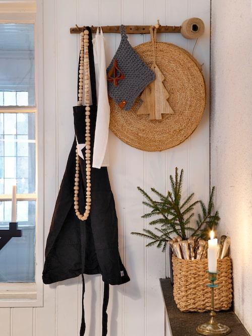 På knoppbrädan, från början en antik kratta, hänger förkläde och grytlappar nära till hands. Förkläde, Design by Pias. Underlägg från Granit.