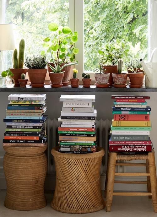 """Rottingpallar och gröna växter ger ett varmt intryck som motvikt till kökets """"maskinpark"""". Här samlas kokböckerna på hög – många av dem gåvor från en journalist i huset som får många, och lägger ut till grannarna att plocka på sig."""