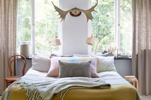 Hemtrevligt, ombonat och mysigt – så sammanfattar Caroline sin inredningsfilosofi, och det stämmer ju bra på sovrummet med dess milda toner. Kuddarna och gardinerna har hon sytt själv, lamporna är modellen Wood av designstudion Taf för Muuto.