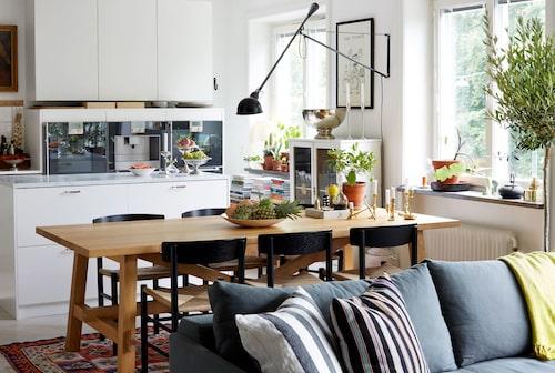 """Kelimmatta och köksbord från Ikea med Wegnerstolar runt om. Lampa, Castiglioni/Flos. Vitrinskåpet är ett gammalt dockskåp från en antikhandel. Tidigare lägenhetsinnehavare var restauratör och satte in kaffemaskin och ångugn, """"Jag kallar det maskinparken"""" säger Caroline och konstaterar muntert att den inte används särskilt flitigt."""