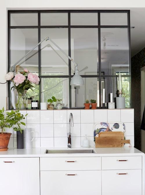 Rumsavdelaren av smide och glas mellan kök och hall är en av de få ändringar familjen gjort sedan de flyttat in för åtta år sedan. De lät också kakla ovanför diskbänken och måla om Ikealuckorna i köket. Lampan är ett auktionsfynd.