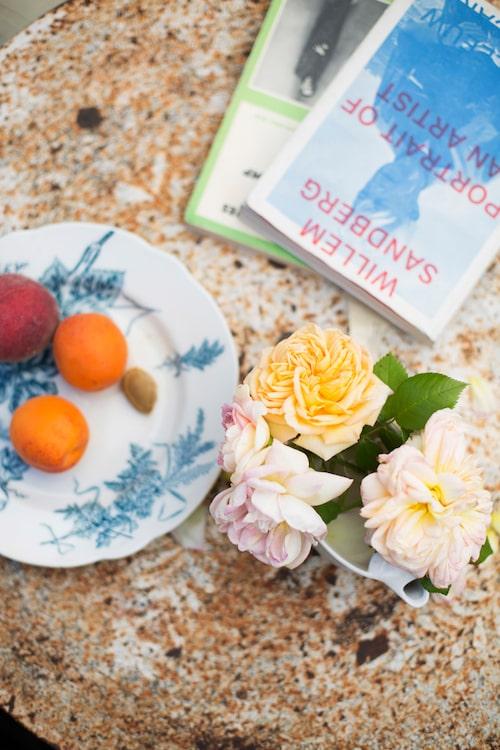 På trädgårdsbordet ligger sommarens litteratur ihop med rosor.