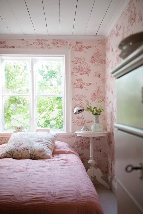 Gästrummet har en rosa toile de jouy-tapet och mycket romantisk känsla. Vas på sängbordet från Venini.
