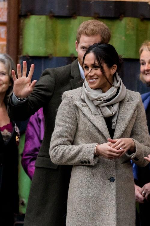 Här syns Meghan Markle med prins Harry vid ett besök på brittiska radiostationen Reprezent i januari med en icke så stram håruppsättning. Kappan är från Smythe.