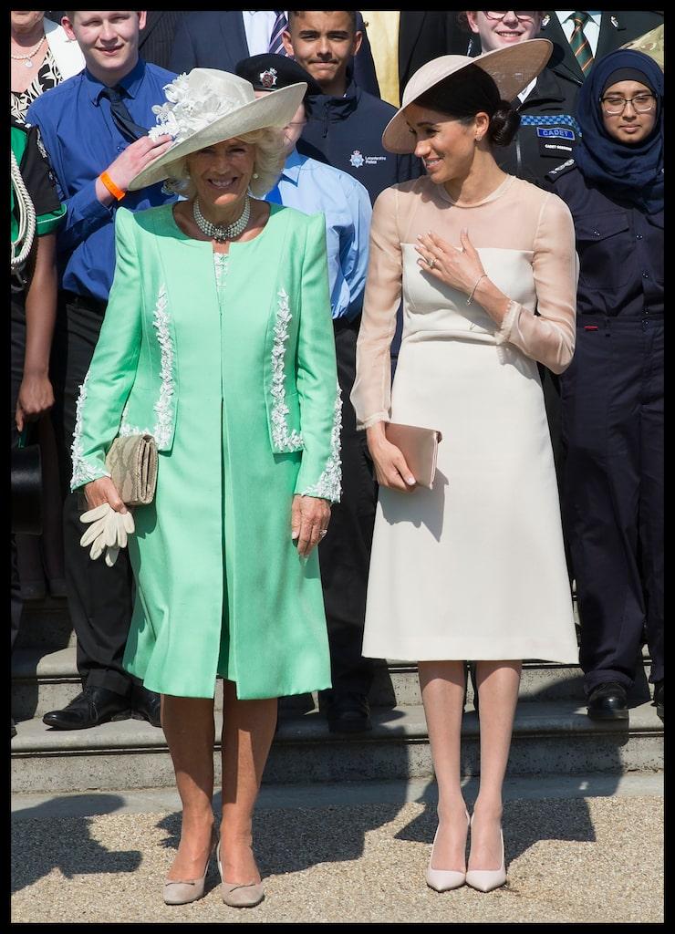 Meghan Markle med strumpbyxor iklädd en nude klänning från Goat i ullkräpp. Bredvid står hertiginnan Camilla i en mintgrön kreation.