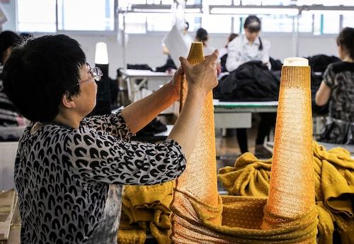 Varje H&M-plagg hanteras av mer än 30 par händer under sin tillverkning. Här letar en anställd i fabriken i Shanghai efter maskor med hjälp av lysrör.