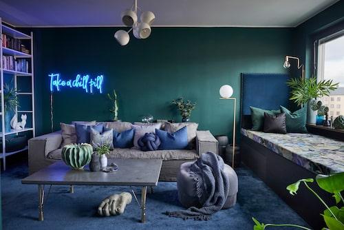 """Klart att vardagsrummet ska vara """"Sarahgrönt""""! Nyansen togs fram speciellt för Sarah och finns att beställa hos Teknos. Möbeln vid fönstren är platsbyggd och fungerar som soffa, utsiktsplats, förvaring och gästsäng. Tyg i dynan, Bloomsbury/Designers guild. Grå puff, Normann Copenhagen ,soffa, Melimeli, bord, Confident living, pumpavas och hand, Posh living, Golvlampan från Flos var Sarahs eget val. Den vita bokhyllan är från Betonggruvan, och keramikräven från Jonathan Adler."""