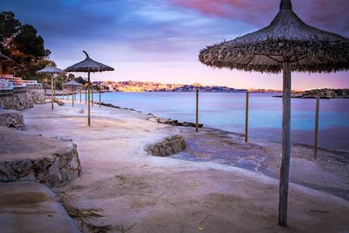 Solnedgång vid stranden Cala Comtesa.