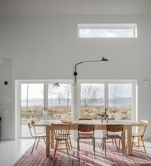 Högt upp på väggen har Sophie och Nikola låtit sätta in ett fönster, som skapar ett härligt överljus. Matbordet har Nikola själv snickrat. Vägglampa, Serge Mouille, och matta, Ikea.