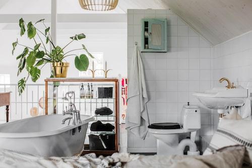 Oj, ingen vägg! Badrumsdelen i sovrummet brukar få gästerna att häpna. Här har man sjöutsikt från badkaret som står fritt i sovrummet. Glasskåpet är ett gammalt tandläkarskåp köpt i en antikhandel i Karlstad.