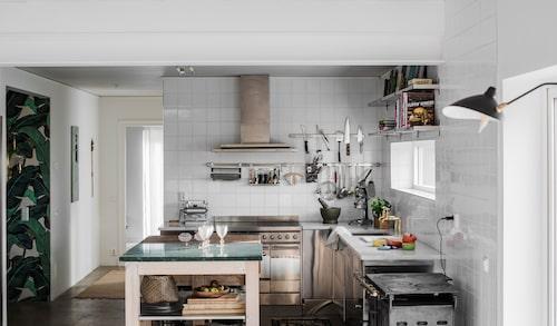 I det öppna köket har man kontakt med både vardagsrum och matsal, ett självklart val då Sophie och Nikola älskar att både laga mat och vara sociala. Arbetsbänken i mitten är ett hembygge där ena delen består av grön marmor och den andra är en rejäl huggkubbe. Spis från Smeg, fläktkåpa från Gaggenau, rostfria hyllor, Ikea.