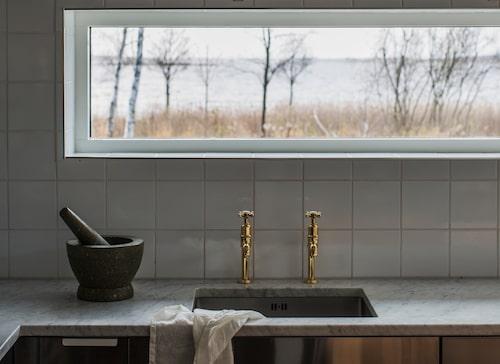 Ovanför diskbänken finns ett liggande fönster för fint ljusinsläpp, och med plats för förvaringshyllor ovanpå. Utsikten blir som en tavla och motivet är sjön Alstern, vassen och de vajande björkarna. De guldglänsande blandarna kommer från Perrin & Rowe, bänkskiva av carraramarmor.
