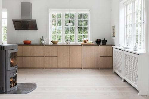 En sprakande braskamin värmer det skandinaviskt stilrena köket.