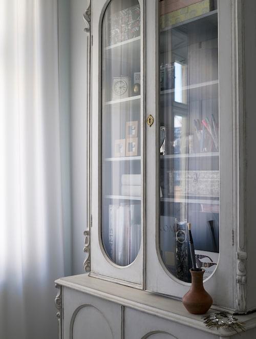 Vitrinskåpet från tidigt 1800-tal fyller en funktion som förvaring i sovrummet.