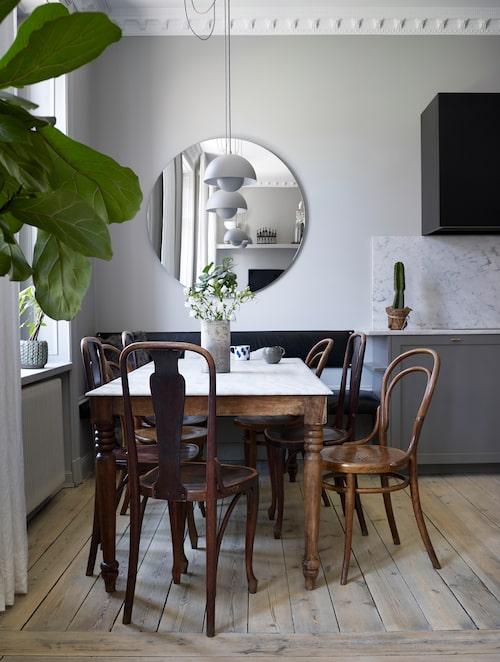 """Det är öppet mellan vardagsrummet och köket med matplatsen. Matbordet är ett gammalt franskt, med stenskiva, """"supersliten, precis som den ska vara"""". Kaféstolarna är olika modeller från tidigt 1900-tal"""