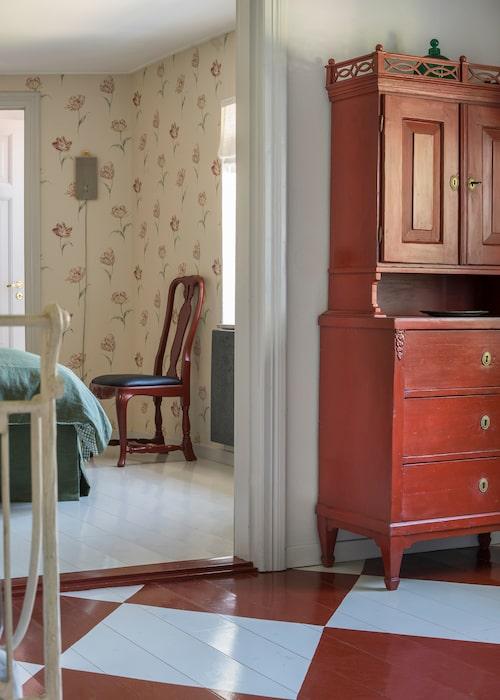 I den lilla salen i gästhuset står ett antikt skåp från Tyskland, köpt via Sonja Ekvall. Golvet är målat i vitt och engelskt rött, med inspiration från en bild i en bok från Gysinge. Rutorna blev ovanligt stora till det lilla rummet…