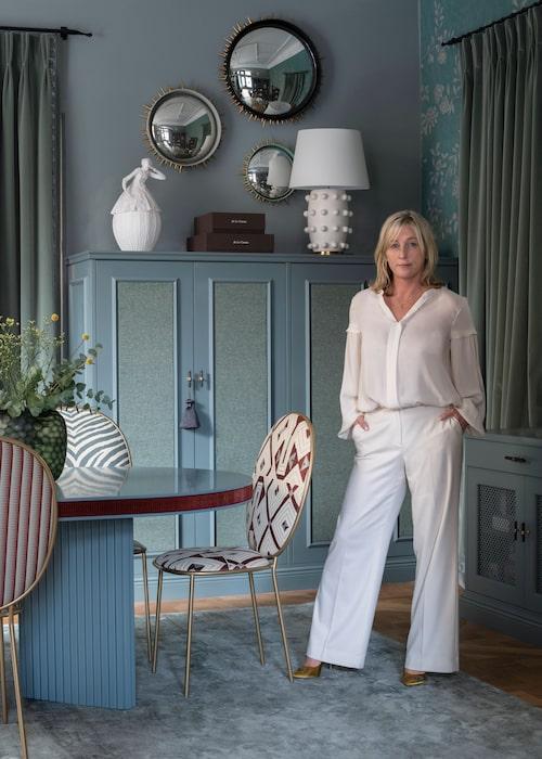 """Sofi Arnholm i sitt hemlika showroom på Nybrogatan i Stockholm. Enfärgad tapet som """"klär in"""" rummet, från Phillip Jeffries, speglar, L'objet, """"taggig"""" bordslampa från Kelly Wearstler/So fine design. Handmålad tapet till höger från De Gournay. Skåpmed textilklädd framsida, i tyg från Astrid, platsbyggda, So fine design."""