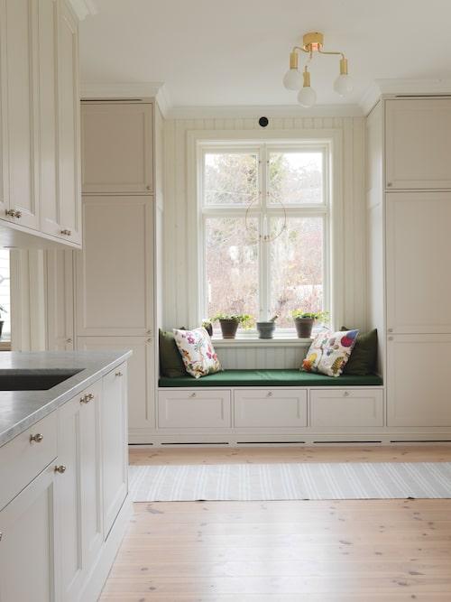 Den platsbyggda kökssoffan vid fönstret är ett fint blickfång och en mysig sittplats. Under soffan finns praktisk förvaring.