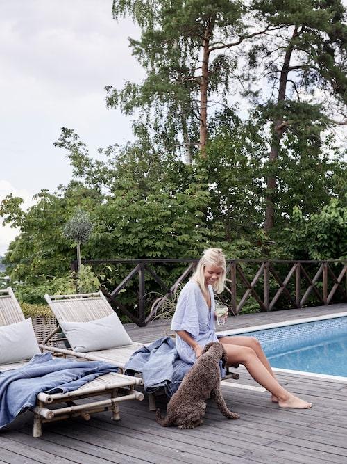 Familjen valde bort garage och la pengarna på en pool i stället. Dottern Lydia och hunden Olle njuter av sol och bad. Solsängar från Granit med denimöverkast från Mio.