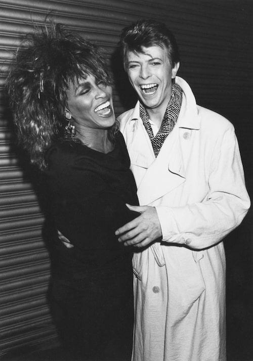 Stilikonerna och goda vännerna David Bowie och Tina Turner i två av basgarderobens trotjänare: trenchcoaten och LBD (Little Black Dress).