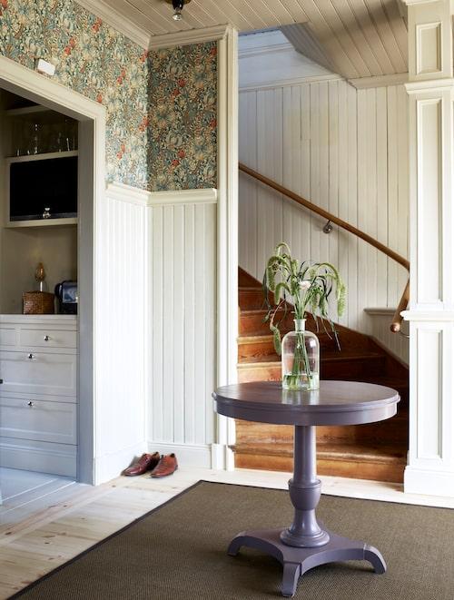 Hallen är husets enda vitmålade rum, och får sällskap av tapeten Golden lily från Morris & co. Trappan till övervåningen har Dexners öppnat upp och en pelare i sekelskiftesstil är byggd intill.