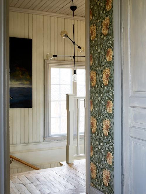 I trapphuset hänger ännu en tavla med ett egenskapat motiv. Väggarna är tapetserade med William Morris-tapeten Pimpernel.