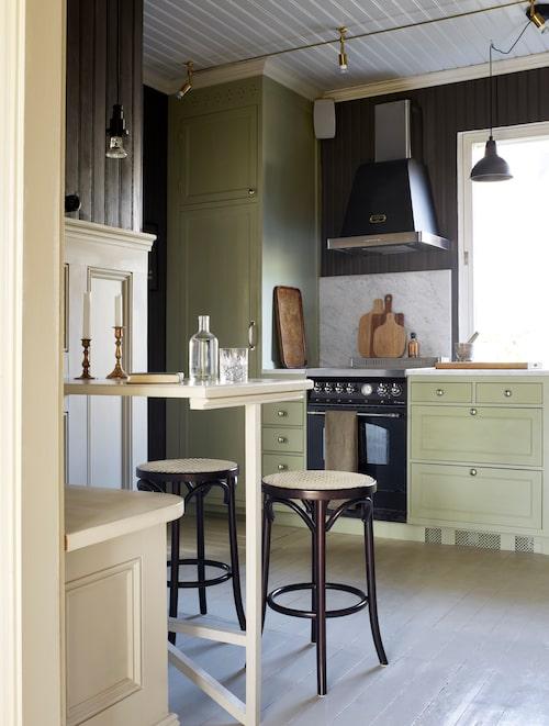 """Det ljusgröna köket har Kalle byggt. """"Symmetri är viktigt för mig, så kylen och frysen placerades på varsin sida om det stora fönstret."""" En liten frukosthörna med pärlgrå panel har paret också byggt, pärlsponten fanns där och målades i samma mörkgrå ton som i taket i matsalen. """"Lite djärvt i ett norrvänt kök, men de ljusgröna luckorna ger värme."""""""