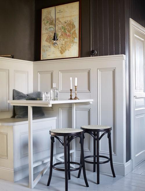 Paret har platsbyggt frukosthörnan med pärlgrå panel. Pallarna är köpta på Blocket och påminner i stil om stolarna i matsalen.