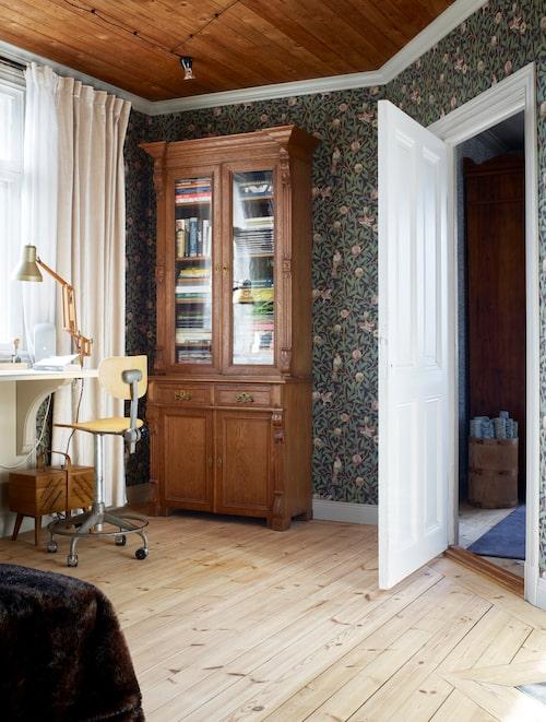 I arbetsrummet på övervåningen står parets älskade vitrinskåp, inköpt när paret bodde i England. Det spontade taket som togs fram fick behålla sin naturfärg. En rolig detalj, tyckte paret och oljade upp det för att få lite lyster. Tapet Bird & pomegranate av William Morris.