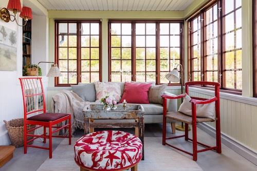 Verandarummet är en favoritplats med ljuset som kommer in från alla håll. Anns favoritdesigner Josef Frank har ritat stolen 2025 i rött, pallen 647 med tyg Aristidia, och rummets samtliga lampor. Temat i rött fortsätter i den ommålade antika stolen till höger. Soffbordet består av ett allmogetråg som Ann hittade i stenlängan, och en snickare har gjort underredet av de gamla brädorna från huset i Gamla stan.